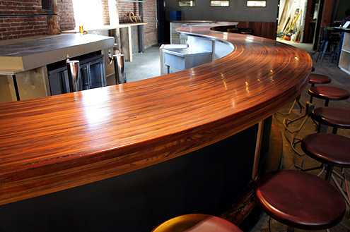 A beautifully hand-crafted wooden bar counter curves alongside exposed brick walls