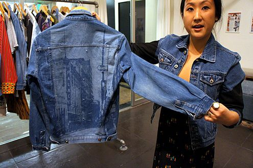 Owner, Janet Sung, holds up a denim jacket personalized with an iPhone cityscape image of Broadway in Downtown LA (an example of denim personalization)